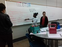 Students complete group activity at the whiteboard