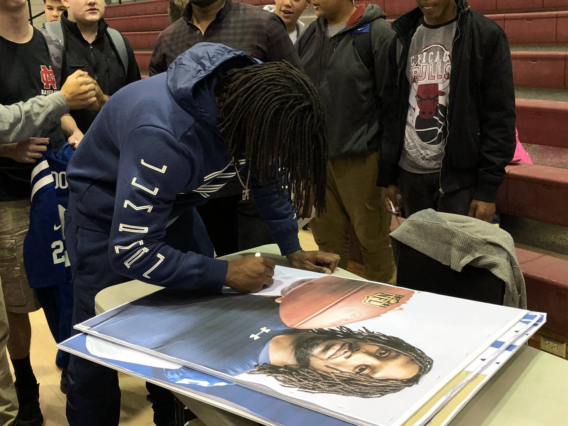 Malik signs posters after the pep rally