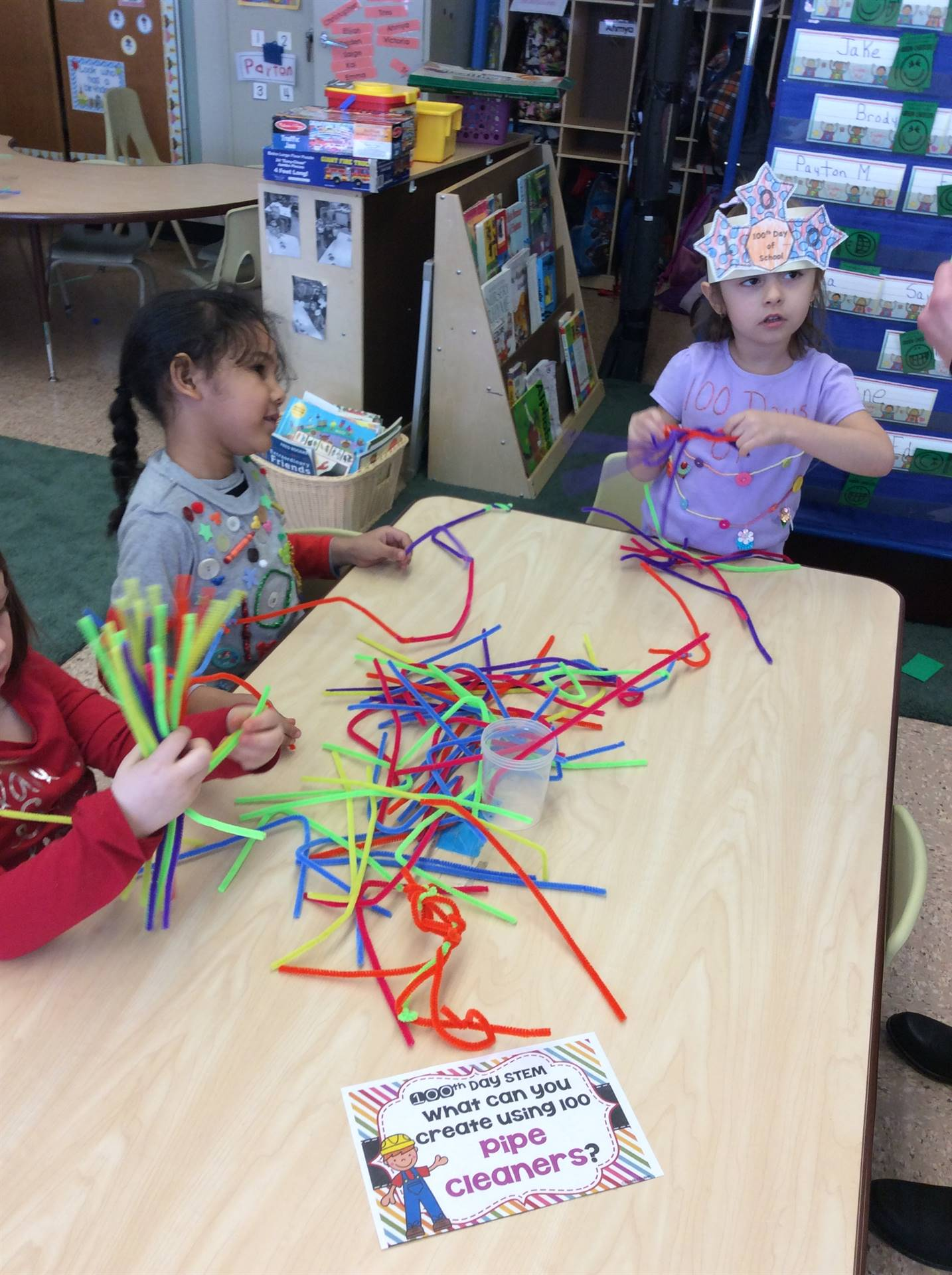 Three pre-k girls attempting to make a Christmas tree with 100 multicolored pipe cleaners