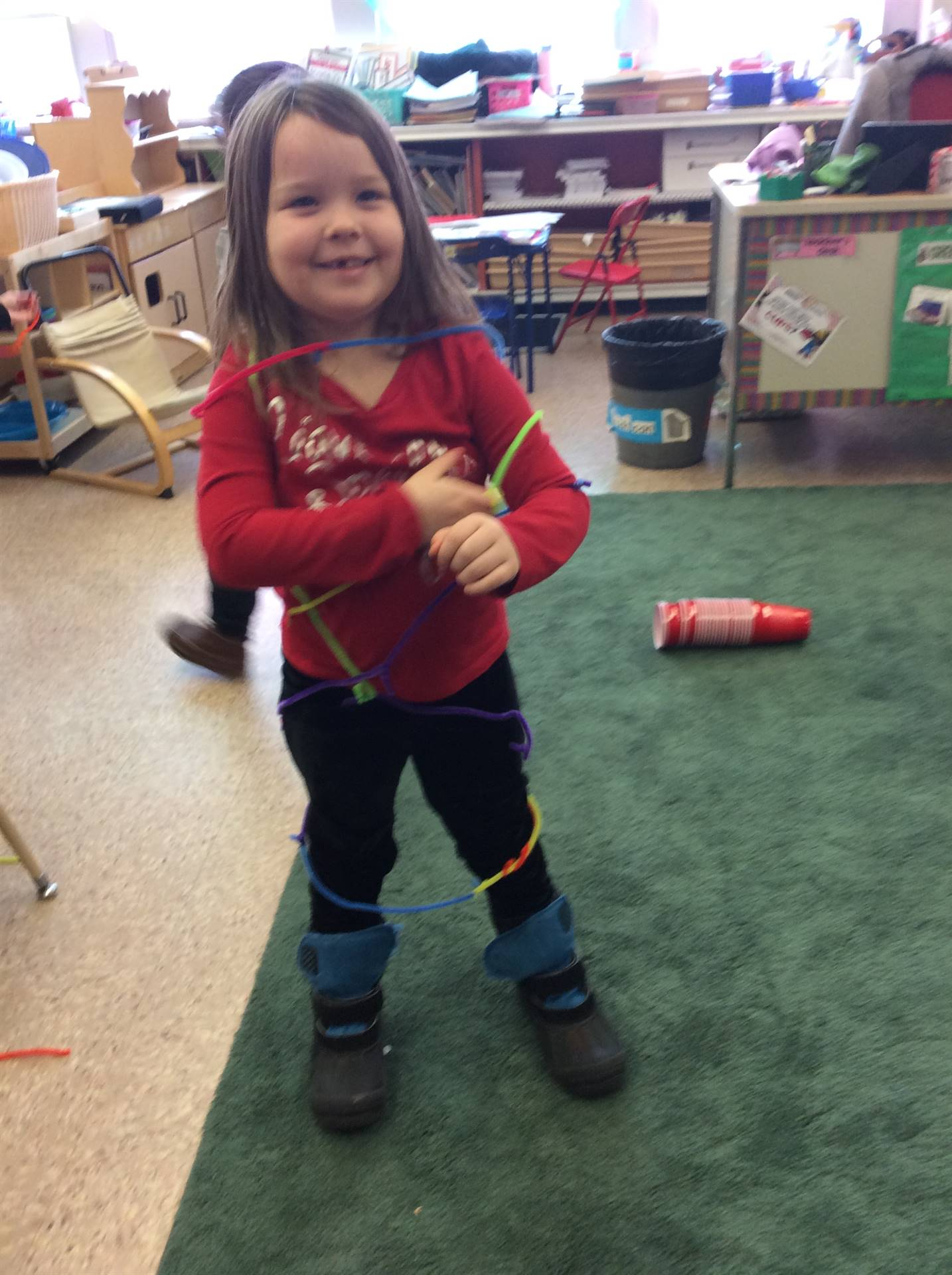 A pre-k girl with a red shirt, black pants, and black and blue boots wrapped in multicolored pipe cl
