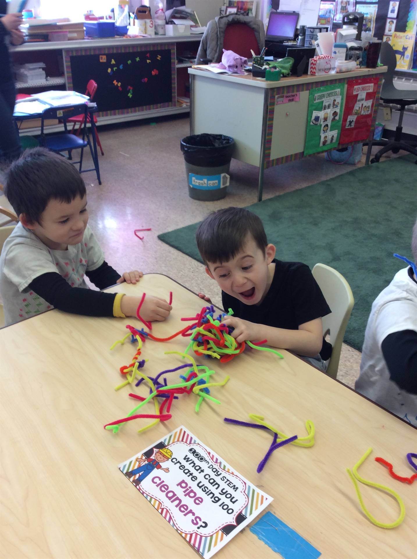 Two boys sitting at a table in their classroom attempting to construct a ball with 100 multicolored
