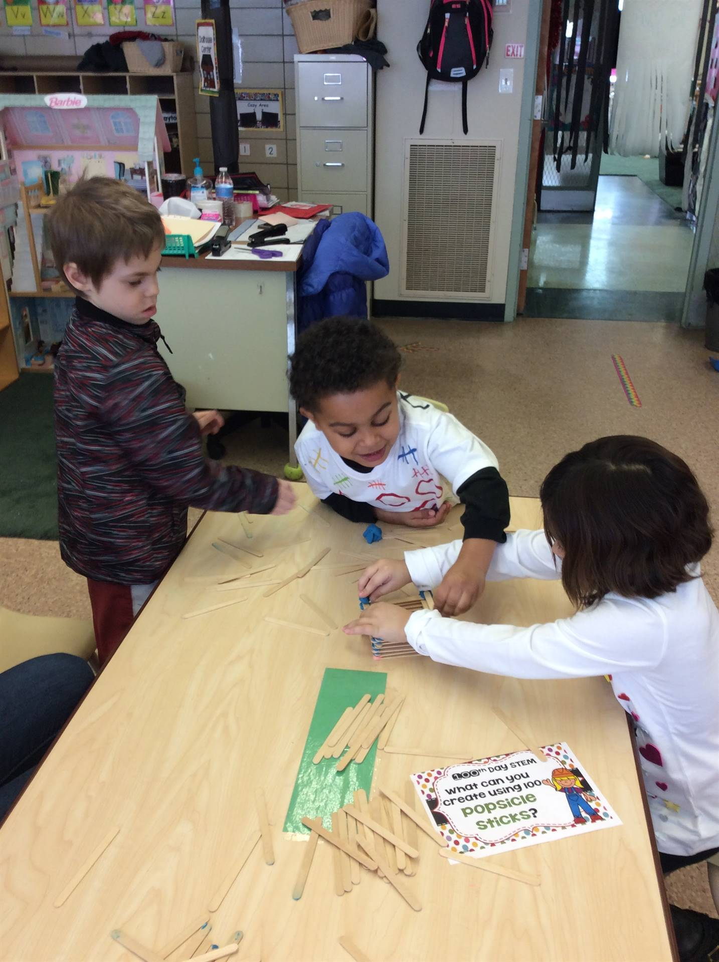 Two pre-k boys and one pre-k girl working together at a table in their classroom to build a tower ou