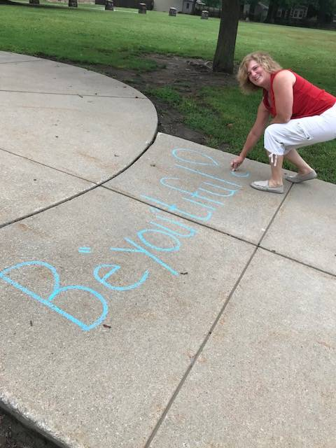 Mrs. Krueger writing an inspirational message to students arriving at school