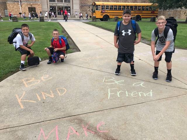 Students entering to chalk inspirational messages at school