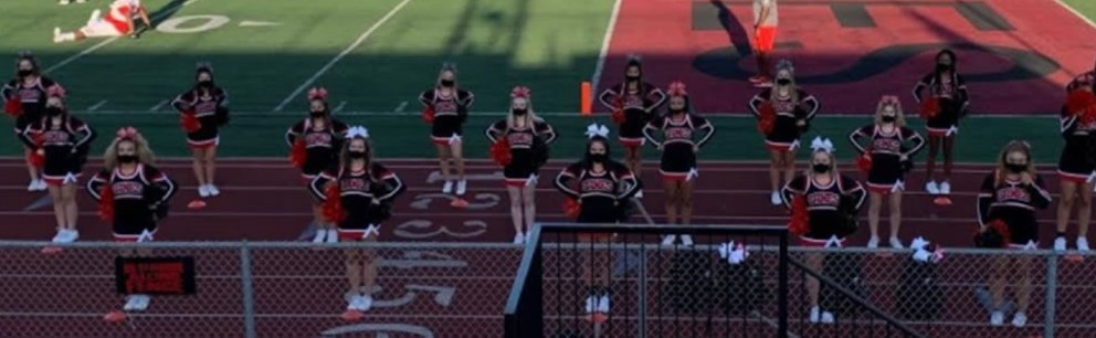 NC varsity cheerleaders with masks performing at football game